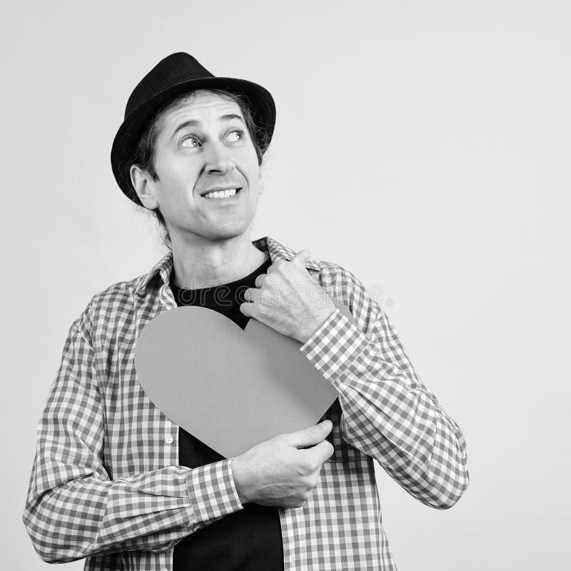 Joyeux jeune homme au coeur rouge Homme amoureux Un homme drôle de chapeau en train de poser en studio Tu me manques, j'ai besoin photos libres de droits