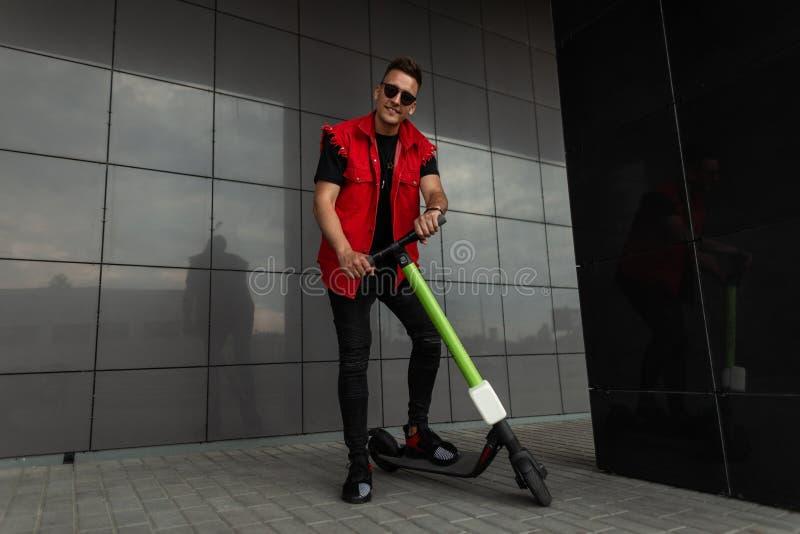 Joyeux jeune homme branché en jeans rouge noir vêtu de baskets sportives dans des lunettes de soleil avec des stands de scooter d image stock