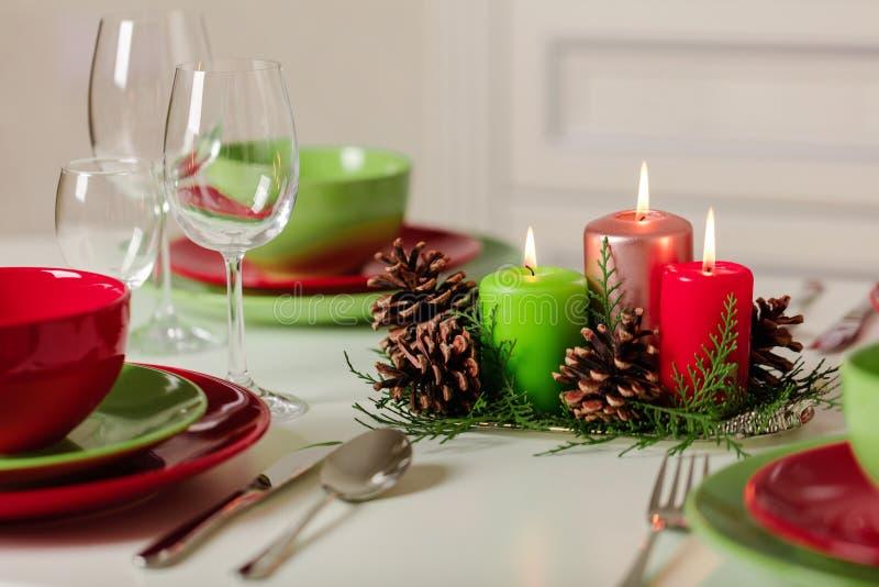 Joyeux Noël et bonne année ! Тable plaçant le décor de fête - plats, bougies et cônes de sapin verts et rouges Décor tricoté - images libres de droits