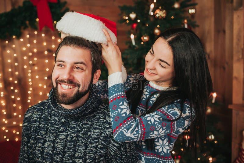 Joyeux Noël et bonne année Jeunes couples célébrant des vacances à la maison Les femmes habille un chapeau de Noël sur a photos stock