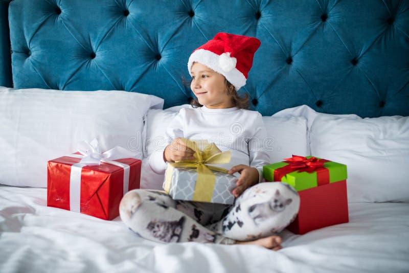 Joyeux Noël et bonnes fêtes Cadeaux de Noël, enfant et concept de vacances La belle fille ouvre un cadeau de Noël de Santa photographie stock