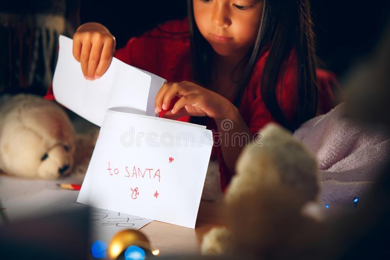 Joyeux Noël et bonnes fêtes La fille mignonne de petit enfant écrit la lettre à Santa Claus près de l'arbre de Noël photographie stock libre de droits