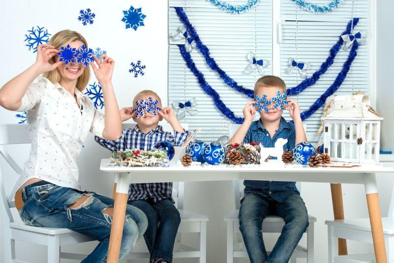 Joyeux Noël et bonnes fêtes ! Mère et deux fils ayant l'amusement tout en créant le décor de Noël photos libres de droits