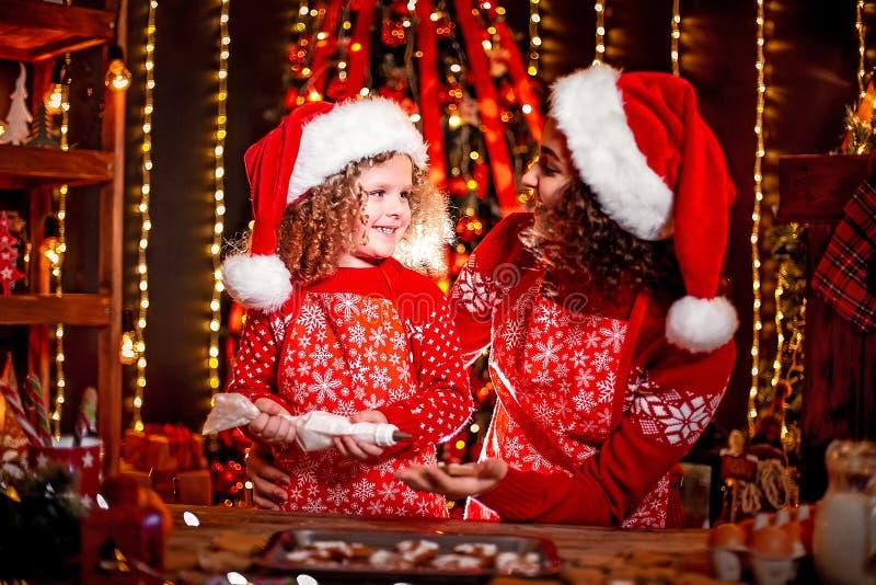 Joyeux Noël et bonnes fêtes Petite fille bouclée mignonne gaie et sa soeur plus âgée dans la cuisson de chapeaux de Santa photos stock