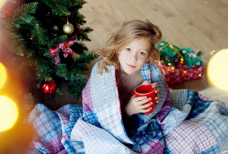 Joyeux Noël et joies fêtes !Le matin de Noël un enfant heureux boit du cacao photos stock