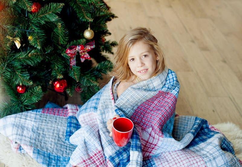 Joyeux Noël et joies fêtes !Le matin de Noël un enfant heureux boit du cacao photo stock