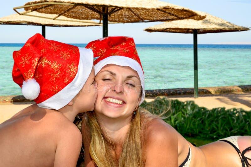 Joyeux Noël La maman et le petit fils se trouvent sur la plage utilisant des chapeaux de Santa et célébrant Noël photographie stock