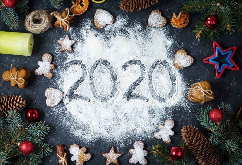 Joyeux Nouvel An 2020 écrit sur la farine et les décorations de Noël Gingerbread cookies Carte de voeux du Nouvel An photographie stock libre de droits