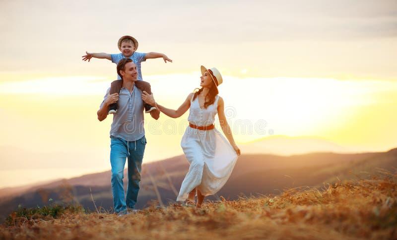 Joyeux père de famille, mère et fils enfant sur la nature au coucher du soleil images stock