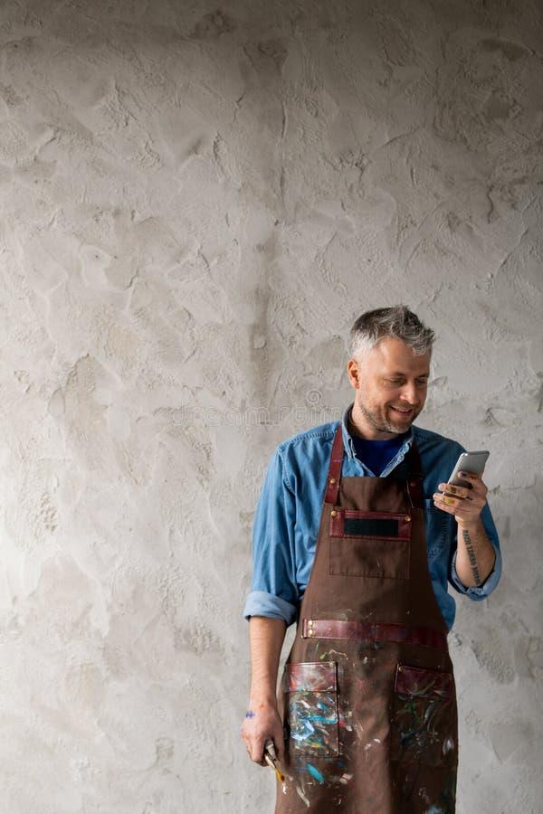 Joyeux peintre professionnel d'âge moyen en tenue de travail défilant dans un smartphone image stock
