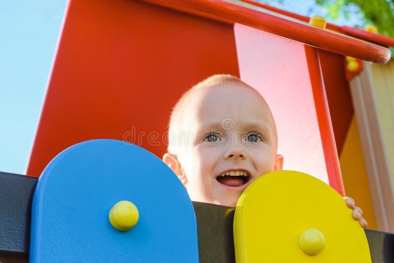Joyeux petit garçon sur l'aire de jeux Jouer à l'extérieur, un garçon riant images stock