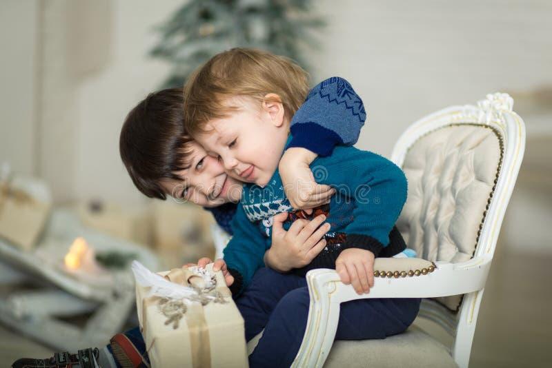 Joyeux petit sourire deux petits frères sur un fauteuil près de l'arbre de noël et tenant la boîte cadeau de noël photos stock