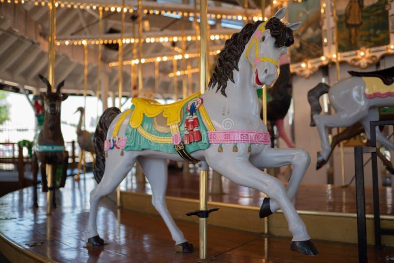 Joyeux s'attaquent le carrousel de poney de rond au parc images libres de droits