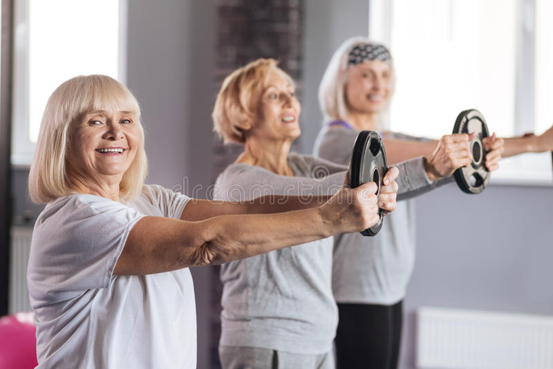 Joyful active woman doing a physical exercise royalty free stock photography