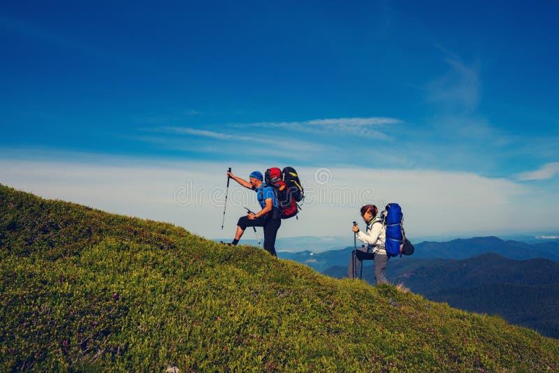 Joyful adventurers having fun. Joyful adventurers with backpacks are walking along green mountain ridge and having fun on the background of blue sky. Epic travel royalty free stock photo