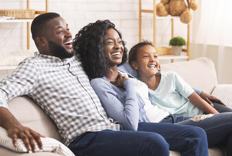Joyful african american family watching comedy show on tv together stock photos