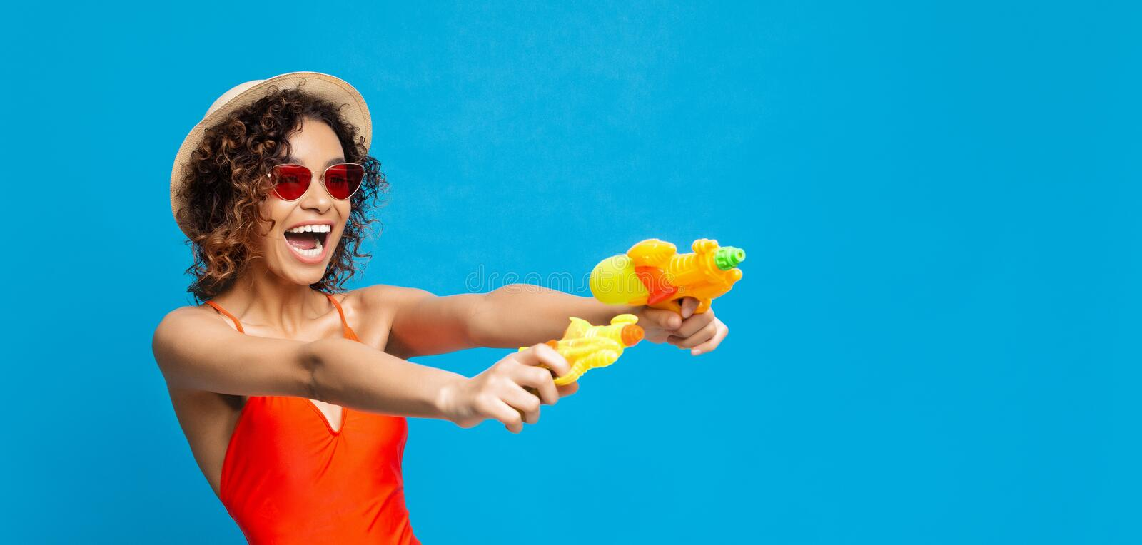 Joyful african american girl with water gun shooting aside at empty space stock photo
