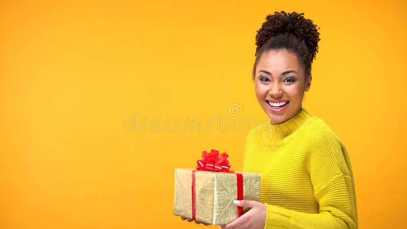 Joyful afro-american female holding present on bright background, happiness royalty free stock photos