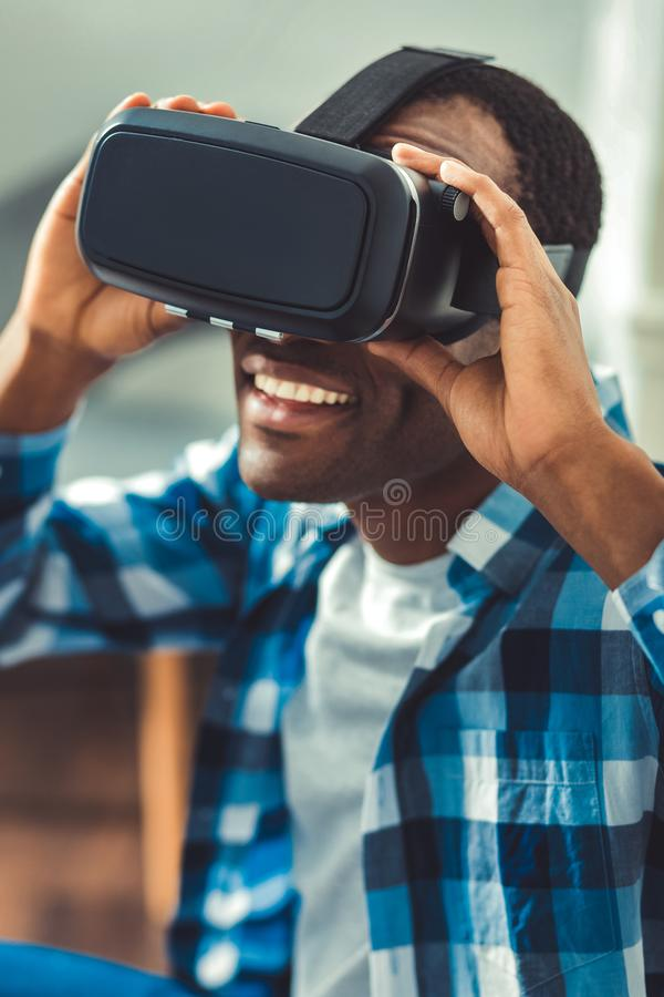 Joyful afro american man impressing by VR. Virtual world. Exuberant afro american man putting on VR glasses and touching them royalty free stock image
