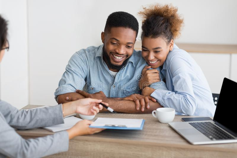 Joyful afro couple sitting at family counselor`s office. Family and adoption counseling. Excited african american couple sitting in psychologist`s office stock photography