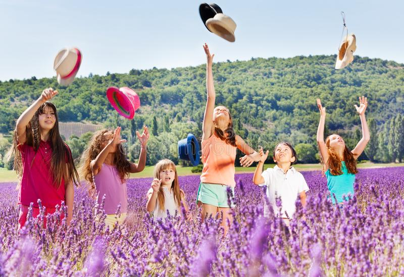 Joyful kids tossing up hats in lavender field. Joyful age-diverse kids standing in lavender field and tossing up hats at summer`s day stock photography
