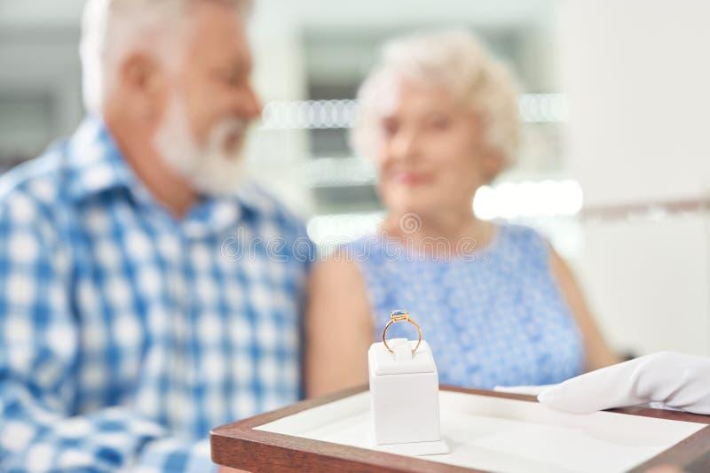 Joyful aged couple buying gold ring with blue gemstone stock images