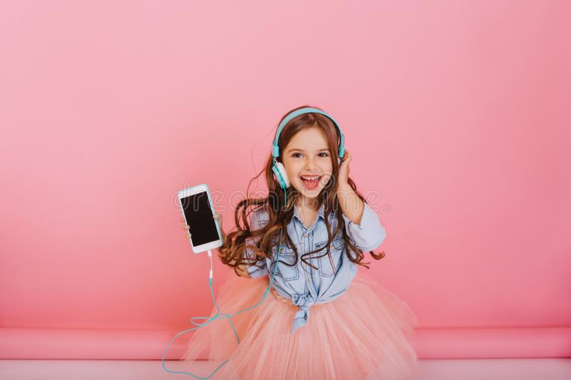 Joyful amazing little girl in tulle skirt listening to music through blue headphones isolated on pink background stock photos