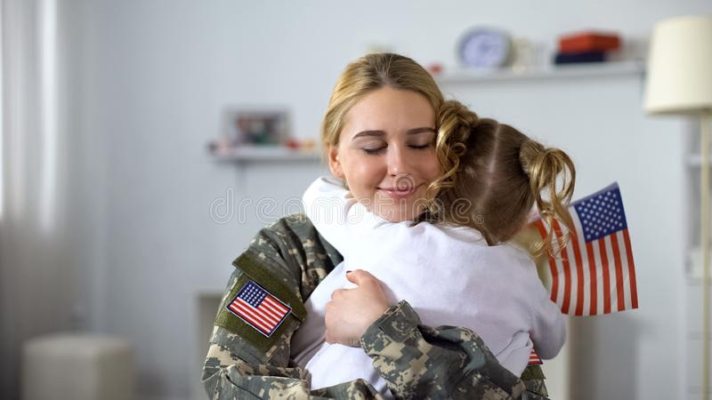 Joyful american soldier woman hugging little sister with national flag, patriot royalty free stock image