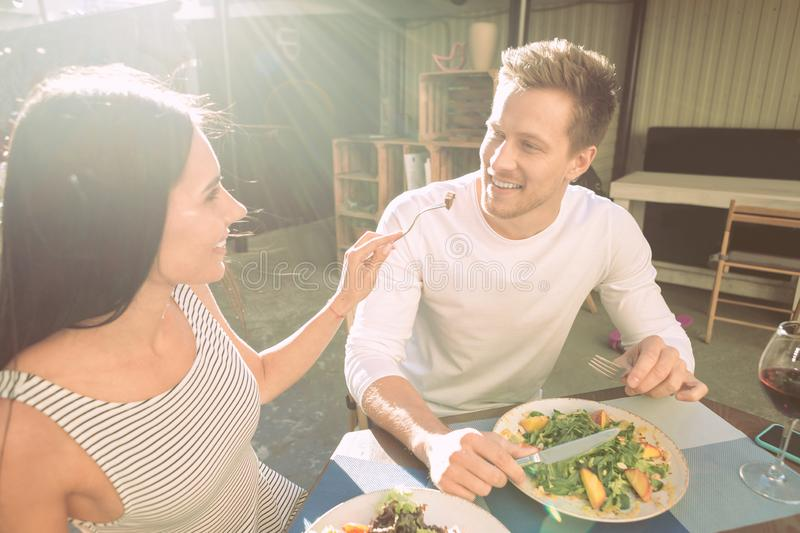 Joyful appealing girl carrying fork with food and proposing to her boyfriend royalty free stock images