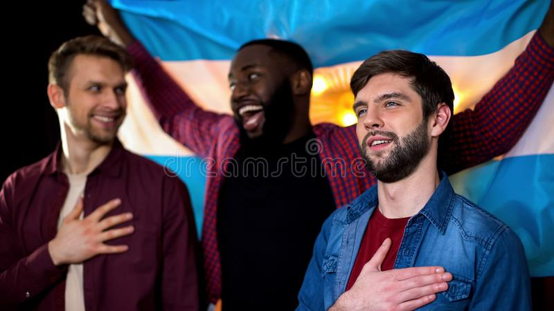 Joyful argentinian fans cheering for football team, singing anthem, waving flag. Stock photo royalty free stock photography