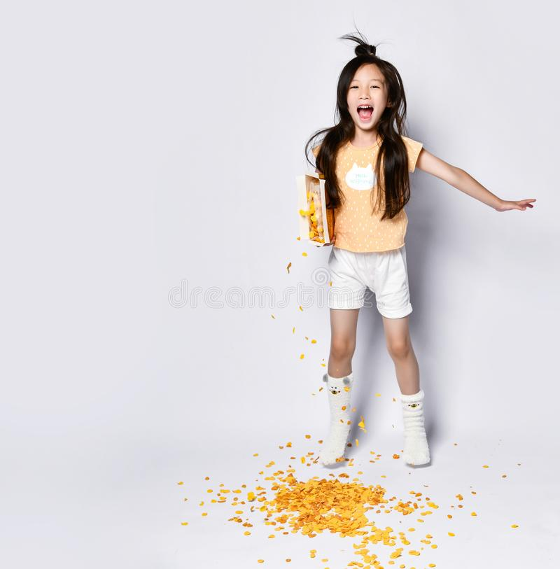 Joyful asian girl kid in home clothes laughs, jumps and does not notice she is spilling out corn flakes on gray royalty free stock photos