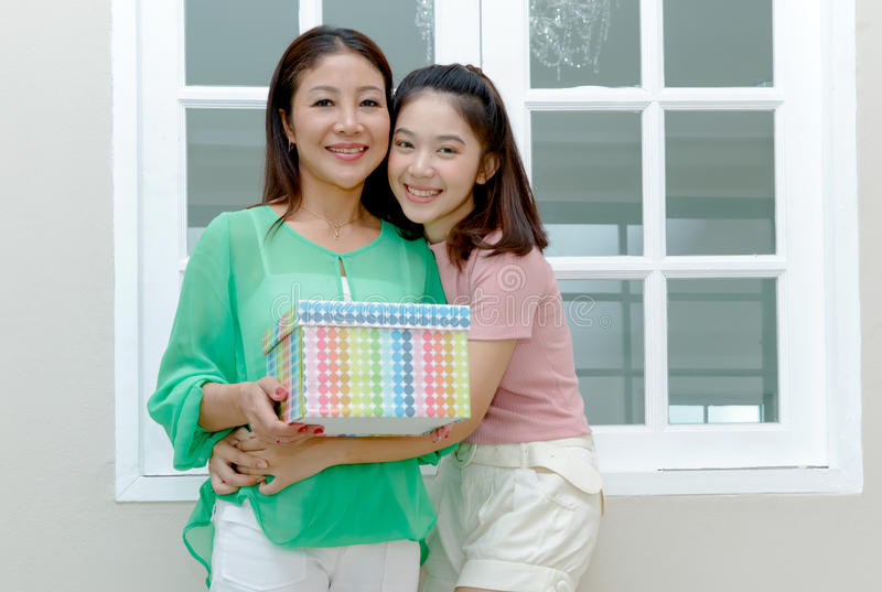 Asian mother and teenage girl holding gift box and smile, royalty free stock photos