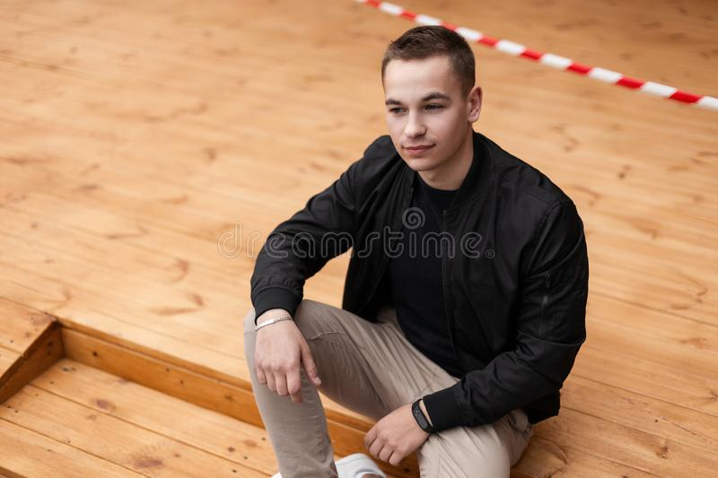 Joyful attractive man in fashionable modern clothes in white sneakers sits and enjoys the rest. Cheerful positive guy relaxes. On wooden steps in the summer royalty free stock image