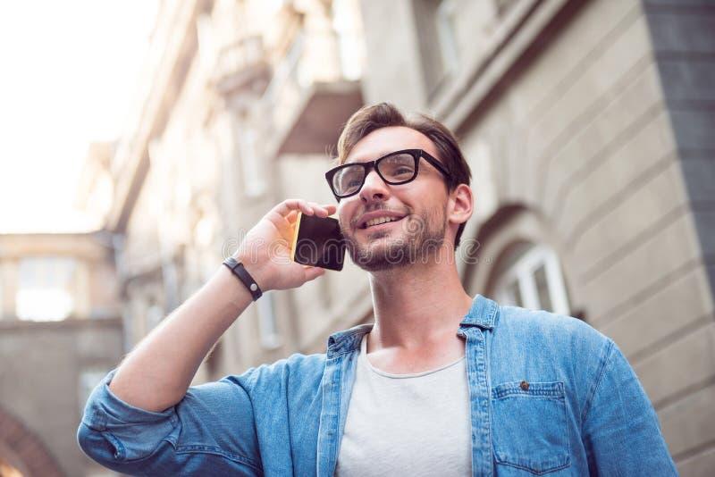 Joyful attractive man speaking on the phone royalty free stock photos