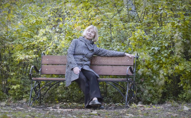 Joyful Autumn. An elderly lady resting on a bench in the park and naslozhdaet warm autumn day and the beauty of the autumn landscape stock image