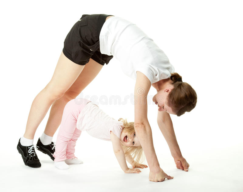 Joyful baby and her mother exercising. Joyful baby girl and her mother exercising; happy mother and daughter doing sport exercises together on white background royalty free stock image