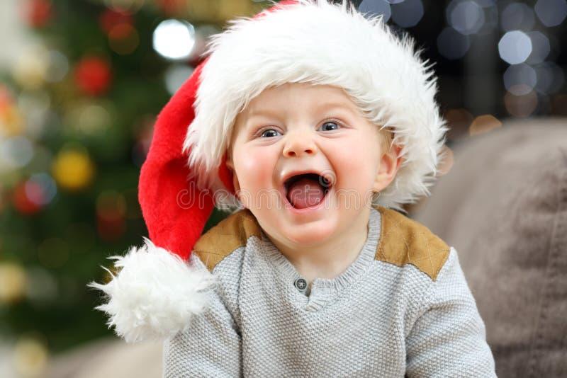 Joyful baby looking at camera in christmas at home stock photography