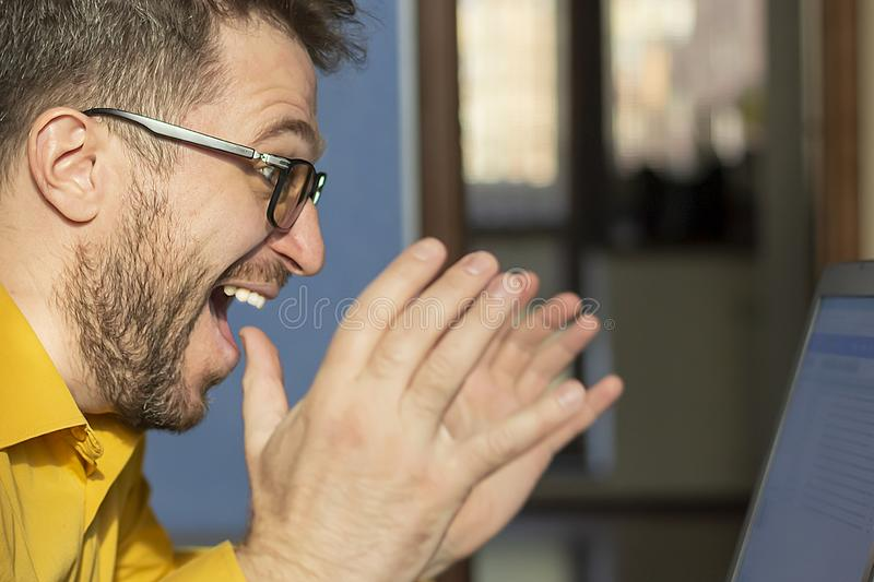 Joyful bearded man with glasses and a laptop at home. royalty free stock image