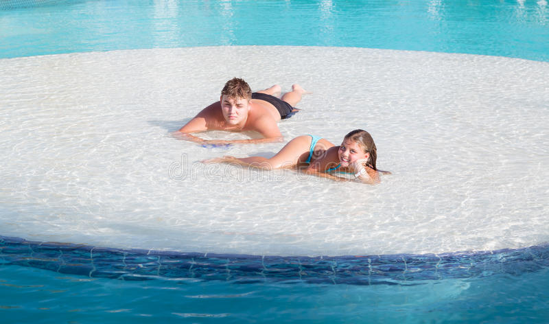 Joyful beautiful smiling little girl and teenage boy relaxing in swimming pool island on summer beautiful gorgeous day stock image