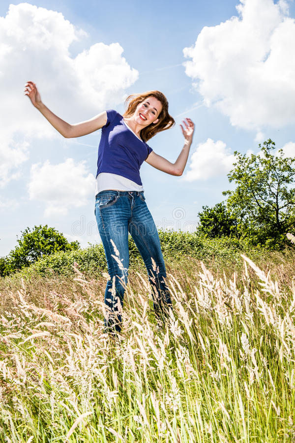 Joyful beautiful young girl jumping, dancing in high dry grass. Joyful beautiful young girl with arms raised jumping and dancing in high dry grass over blue royalty free stock photo