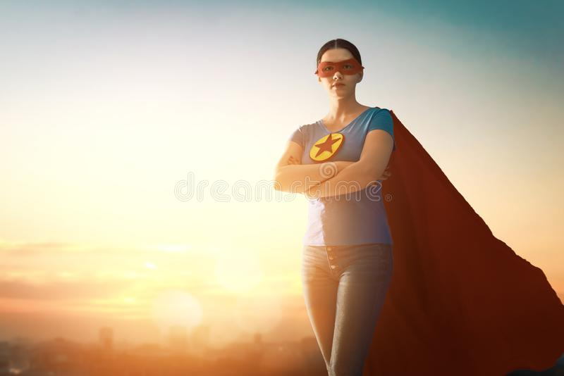 Woman in superhero costume. Joyful beautiful young woman in superhero costume posing on sunset background royalty free stock photo
