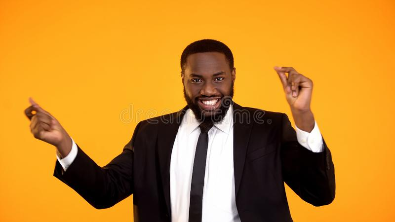 Joyful black businessman making dancing movements successful deal rich and sexy. Stock photo royalty free stock photo