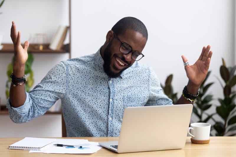 Joyful black businessman talking with friend make video call stock images