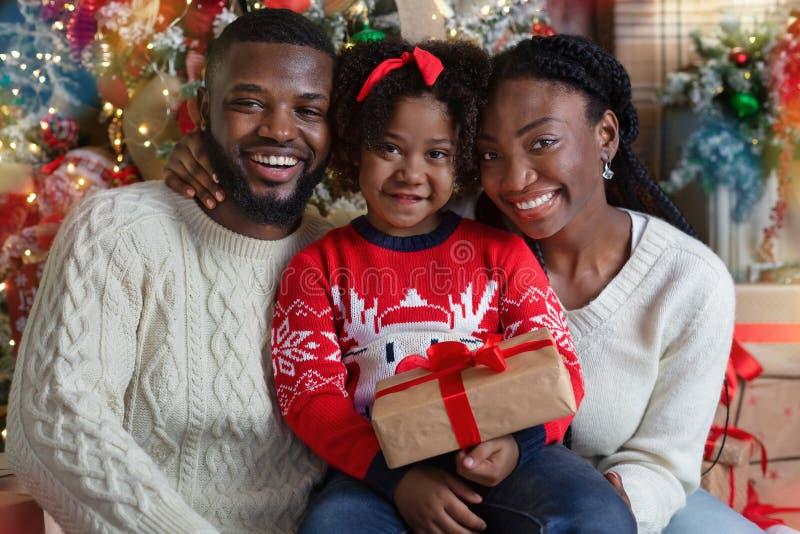 Joyful black family of three posing with gift near Christmas tree stock images
