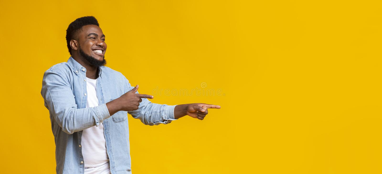 Joyful black guy pointing two fingers aside at copy space. Good Mood Guaranteed. Joyful african american guy pointing two fingers aside at copy space over yellow stock photography