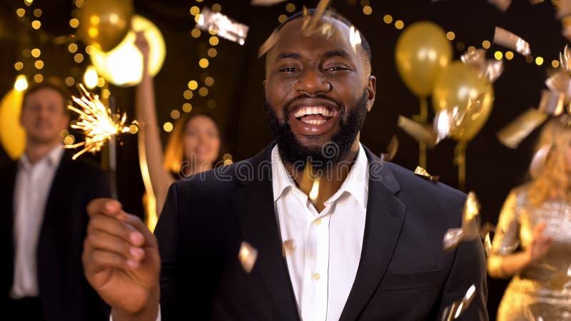 Joyful black male holding bengal light in hand smiling camera, festive event. Stock photo stock images