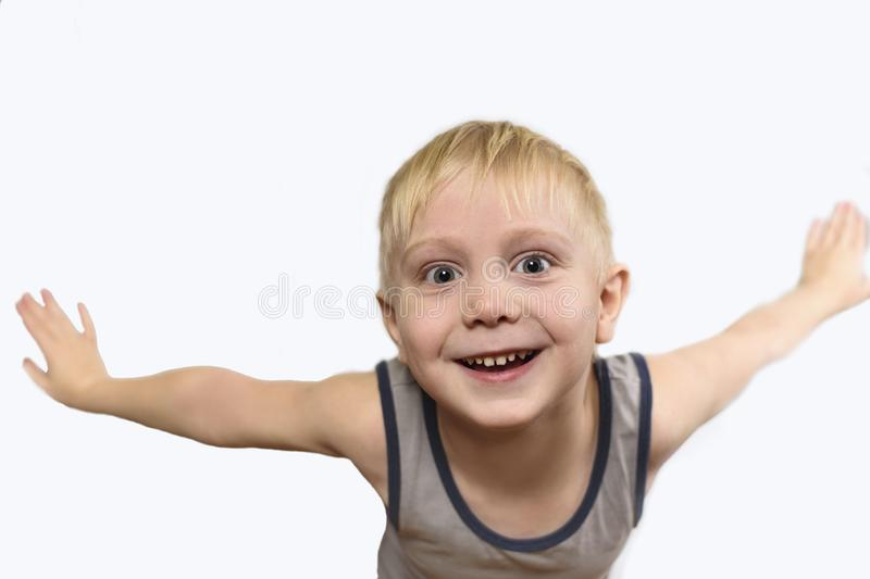 Joyful blond boy in shirt standing arms to the side. Isolate on white background.  stock photos