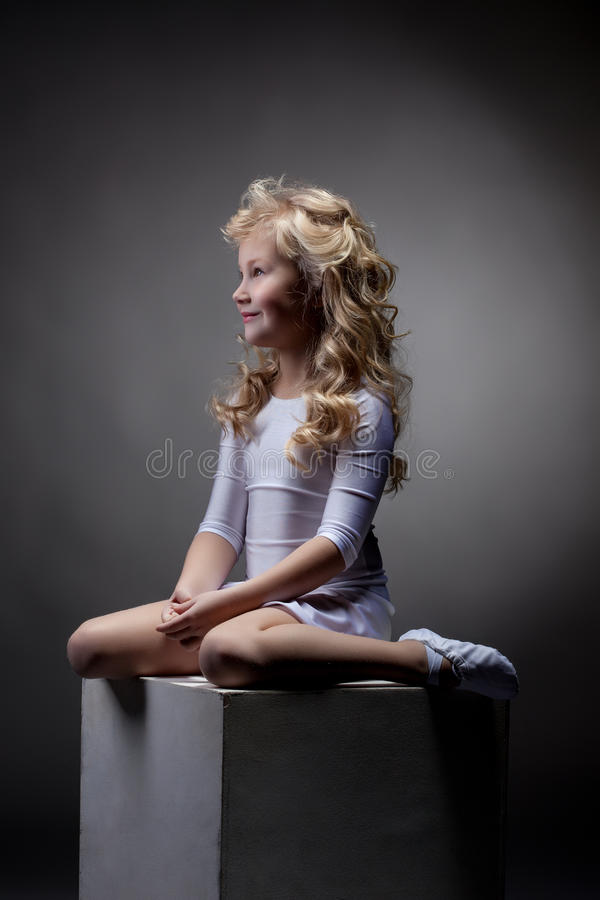 Joyful blonde gymnast posing on cube in studio royalty free stock photos