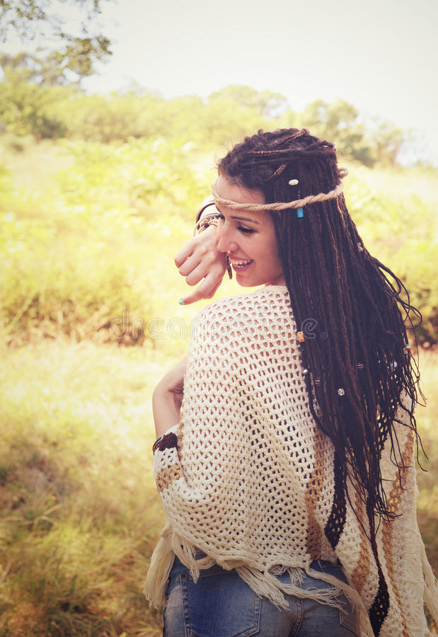 Joyful boho style girl portrait, dressed in knitted poncho and headband have a fun against sunny autumn park, royalty free stock photography
