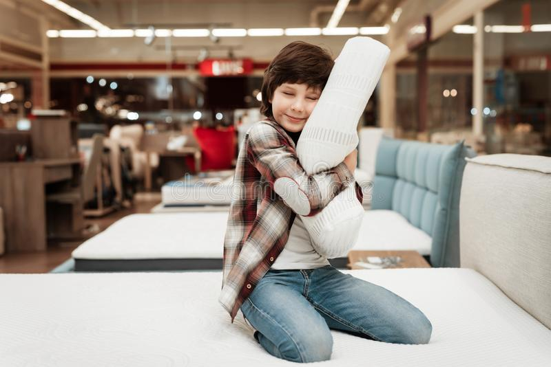 Joyful boy enjoying softness of orthopedic pillow rejoices in furniture store. Joyful little boy hugs orthopedic pillow sitting on mattress stock images